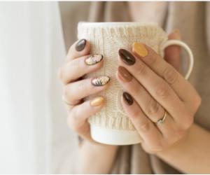 mani con nail art sui colori del marrone ed ocra che impugnano una tazza bianca